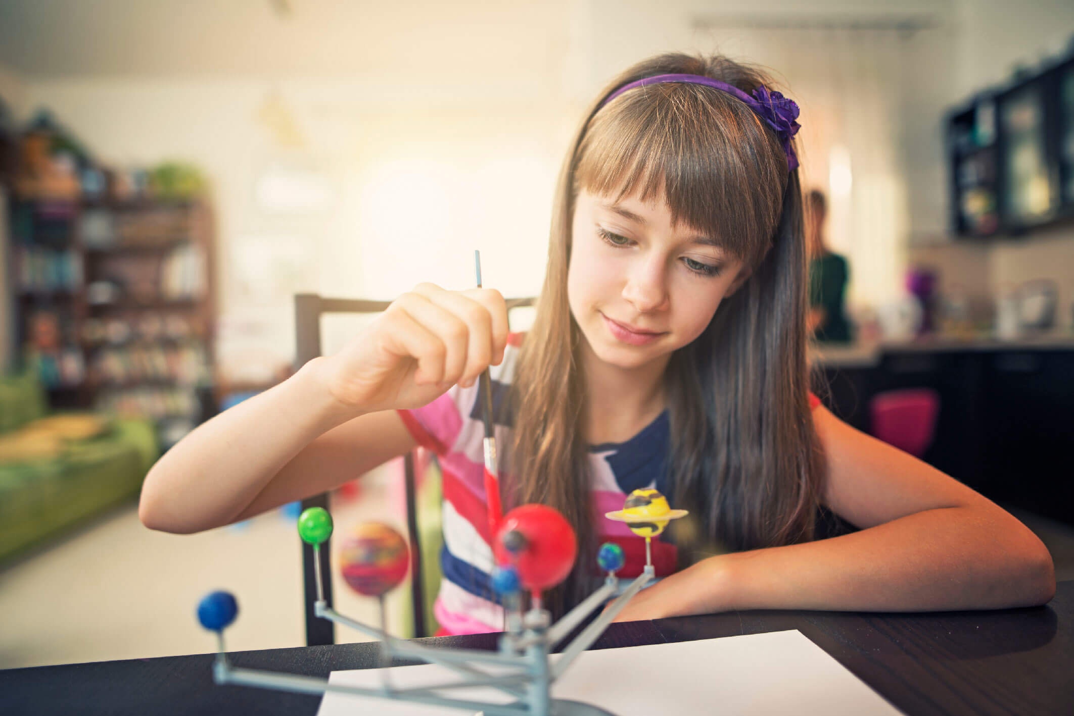 Little girl painting solar system model